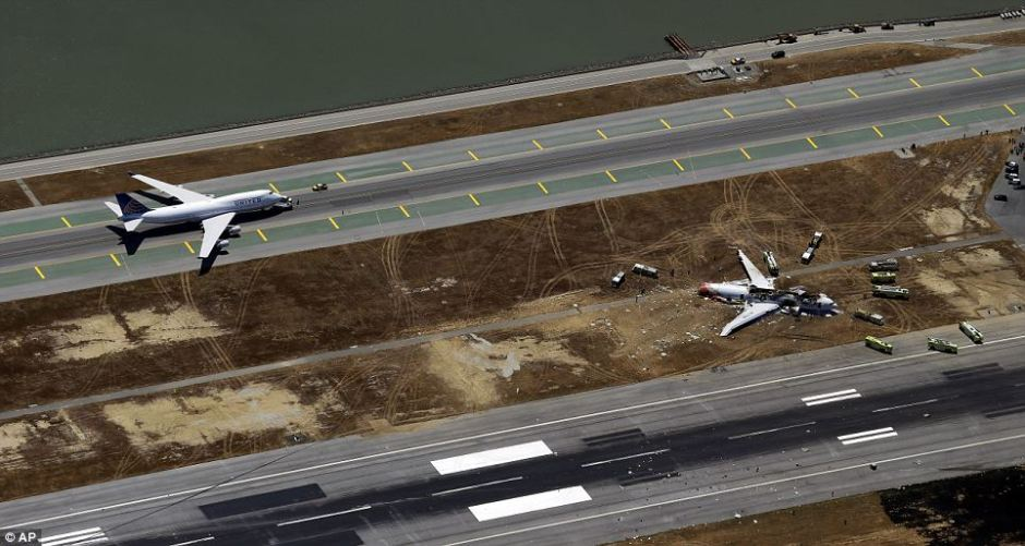 United Airlines 885 is towed back to the terminal past the wreckage of Flight 214.