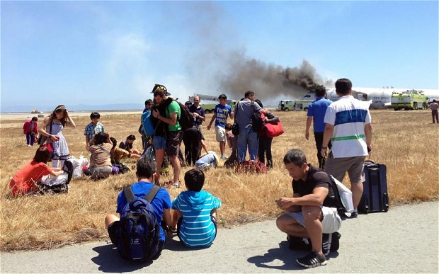 Passengers sit in shock after evacuating the burning jet.