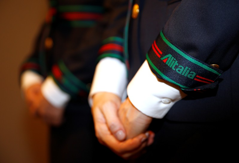 Alitalia airline crew members pose with new uniforms during the official presentation of Alitalia's new Alberta Ferretti-designed uniforms in Milan